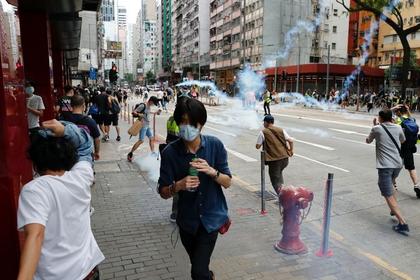 Manifestantes pro-democracia buscan refugio después de que la policía disparara gas lacrimógeno durante una marcha por las calles de Hong Kong en contra del plan de Beijing de imponer una ley de seguridad nacional. REUTERS/Tyrone Siu